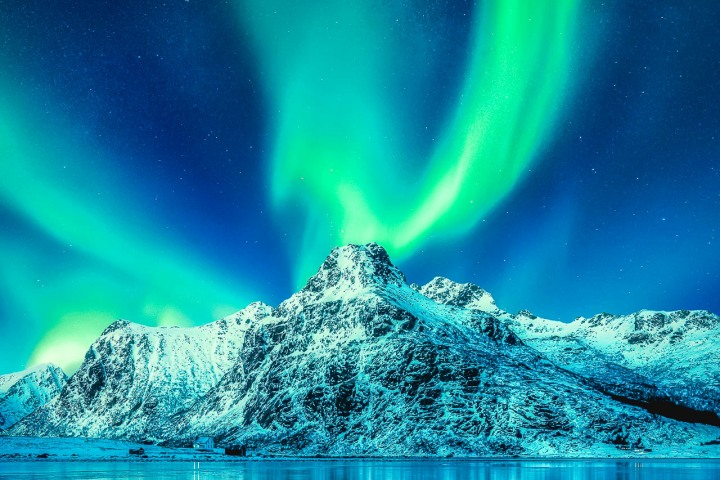 Aurora Borealis, Lofoten islands, Norway. Northen lights, mountains and reflection on the water. Winter landscape during polar lights. Norway travel - image